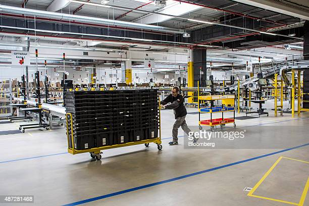 An employee moves a cart loaded with empty product crates through the shipping zone on the opening day of the new AmazonCom Inc fulfillment center in...