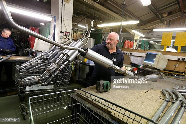 An employee moves a completed automobile catalytic converter emission control device at BM Catalysts in Mansfield UK on Wednesday Sept 30 2015...