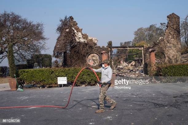 An employee moves a hose in front of the Signorello Estate wine tasting room burned by wildfires in Napa, California, U.S., on Friday, Oct. 13, 2017....