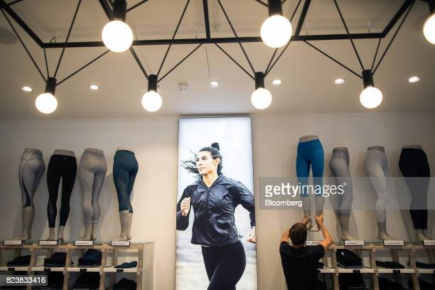 An employee moves a mannequin displaying a pair of leggings at the Lululemon Athletica Inc sports apparel store on Regent Street in London UK on...