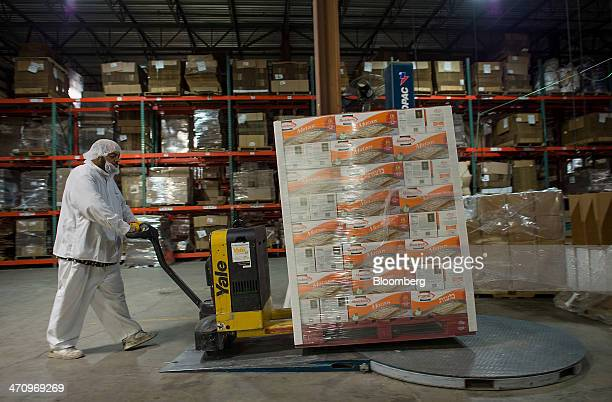 An employee moves a palette of five pound cartons of Passover matzo at the Manischewitz Co factory in Newark New Jersey US on Thursday Feb 20 2014...