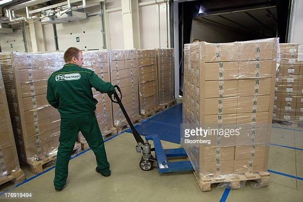 An employee moves a pallet truck loaded with boxed pharmaceuticals around the storage facility ahead of shipping at OAO Pharmstandard's Leksredstva...