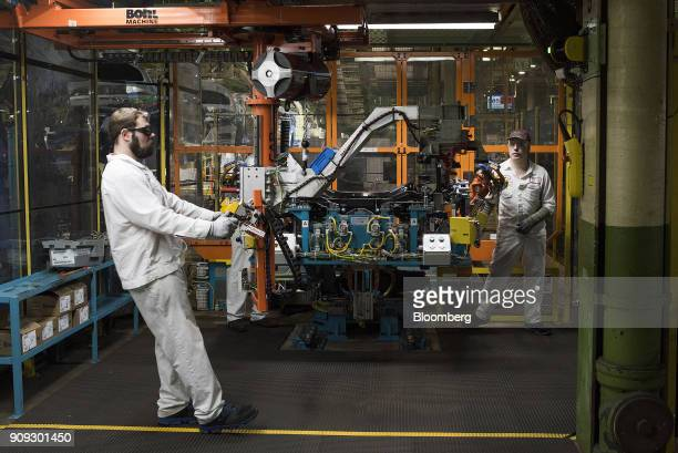 An employee moves a part into the rear suspension feeding the robotic assembly during production at the Honda of America Manufacturing Inc Marysville...