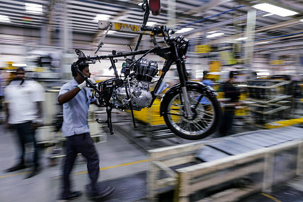 An employee moves a Royal Enfield Motors Ltd Classic 350 motorcycle along the production line at the company`s manufacturing facility in Chennai...
