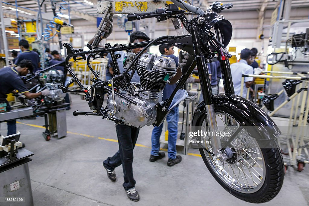 An employee moves a Royal Enfield Motors Ltd Thunderbird Twinspark engine attached to the chassis of a Classic 350 motorcycle along the production...