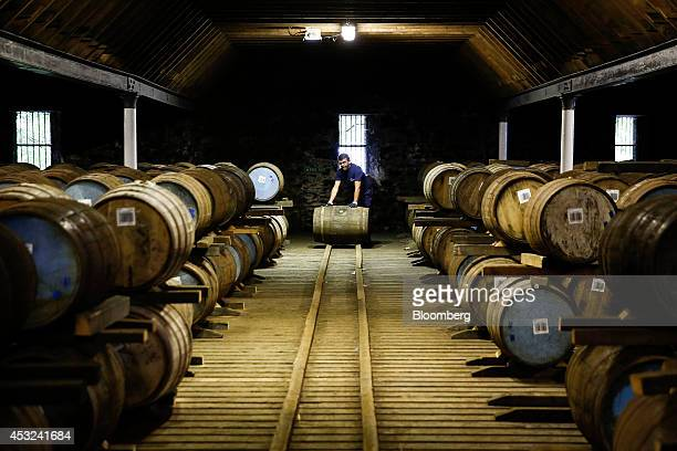 An employee moves a wooden cask of Chivas Regal blended Scotch whisky produced by Pernod Ricard SA at the company's Strathisla distillery in Keith UK...