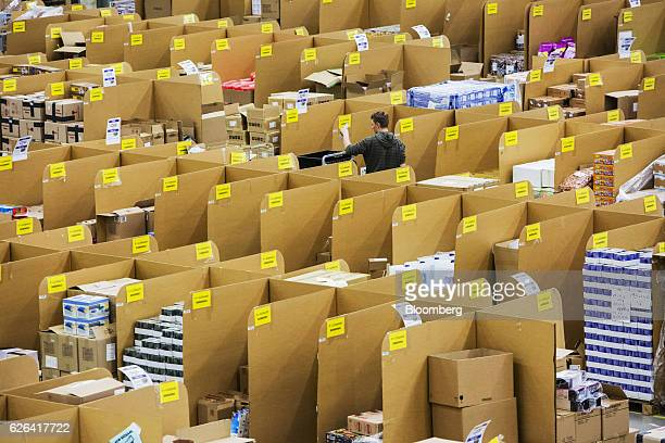 An employee moves between stacked boxes and parcels ahead of shipping from the warehouse of an Amazoncom Inc fulfillment center in Koblenz Germany on...