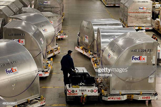 An employee moves cargo containers inside the FedEx Corp distribution hub at Los Angeles International Airport in Los Angeles California US on Monday...
