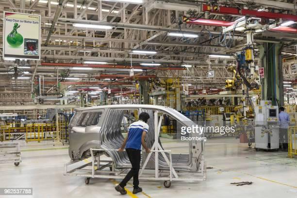 An employee moves door plates for Mahindra Mahindra Ltd TUV 300 sportutility vehicles on the production line at the company's facility in Chakan...