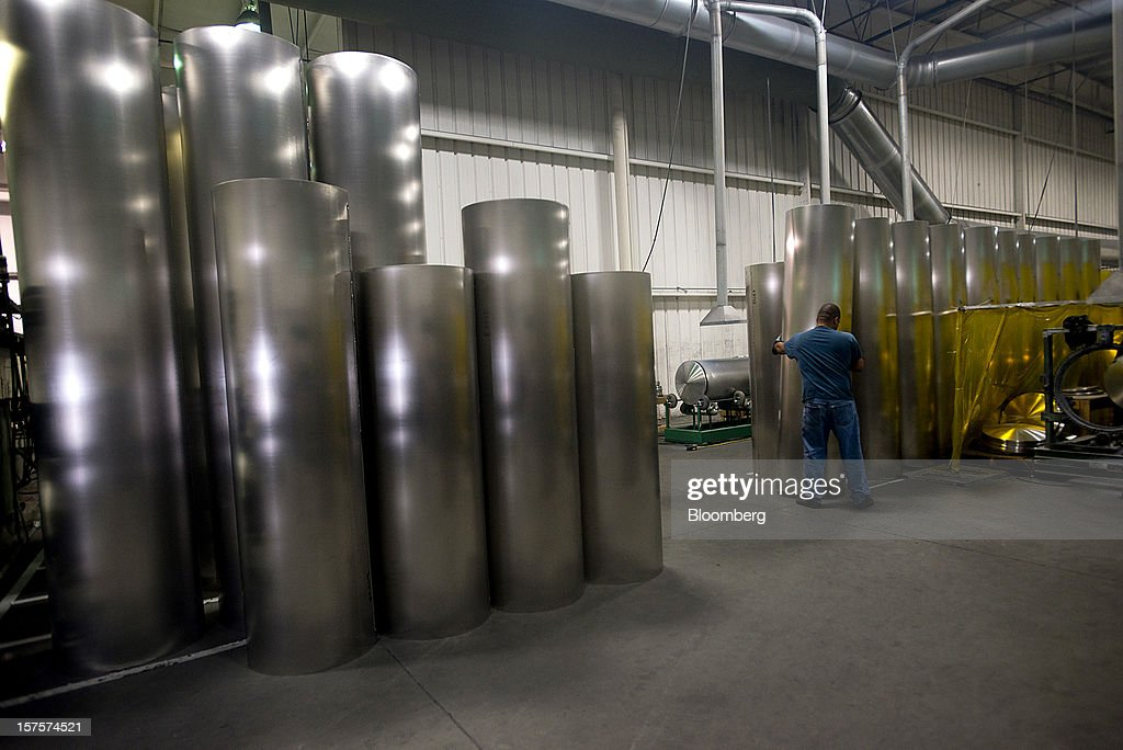 An employee moves rolled sheets of aluminum to be used as shells for the pontoons at the Nautic Global Group production facility in Elkhart, Indiana, U.S., on Tuesday, Dec 4, 2012. The U.S. Census Bureau is scheduled to release factory orders data on Dec. 5. Photographer: Ty Wright/Bloomberg via Getty Images