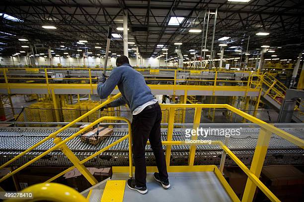 An employee nudges a box moving along a conveyor belt at the Amazoncom Inc fulfillment center on Cyber Monday in Robbinsville New Jersey US on Monday...