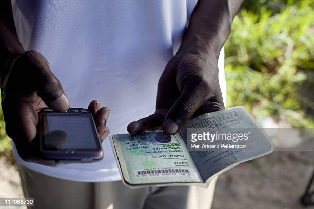 An employee of a bank checks an identity document via mobile phone as he sells accounts on the street on May 5 2011 in Khayelitsha the poorest and...