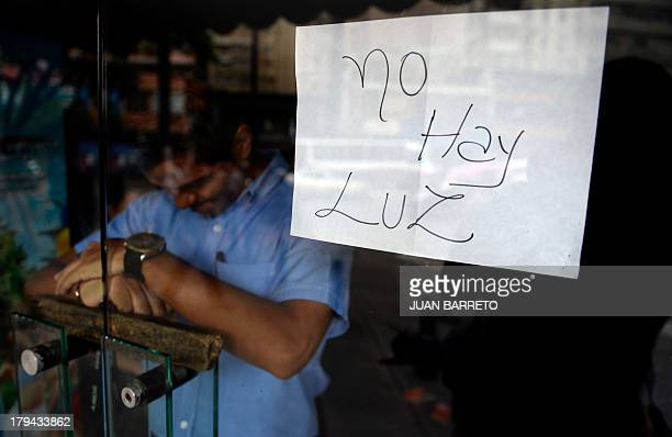 An employee of a business closed during a blackout stands behind the door with a notice reading There's No Light in Caracas on September 3 2013 Major...