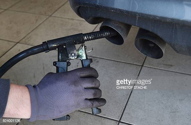 An employee of a car workshop checks the emission levels of a vehicle in Eichenau southern Germany on April 25 2016 Major names in the auto industry...