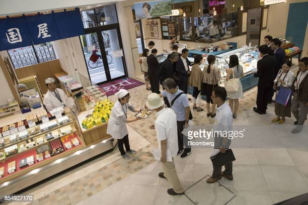 An employee of a confectionery store offers tasting samples during a media tour of the Trie Keio Chofu Shopping Center operated by Keio Corp in Chofu...