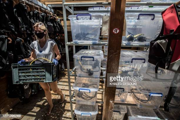 An employee of a diving center moves equipment at the Red Sea resort of Sharm elSheikh on June 20 during a visit by the Egyptian Minister of Tourism...