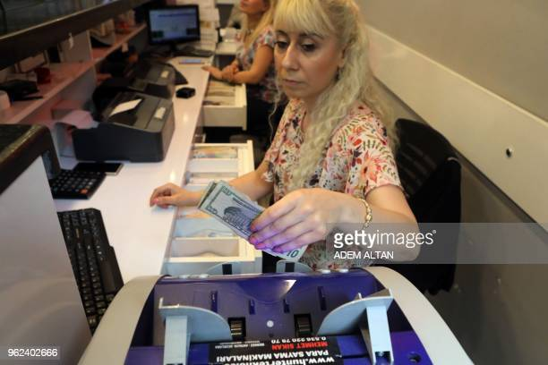 An employee of a foreign exchange office removes US dollars banknotes from a machine in the centre of Ankara on May 25, 2018.