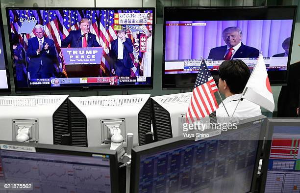 An employee of a foreign exchange trading company looks at monitors displaying TV news of Republican Presidentelect Donald Trump as he gives his...