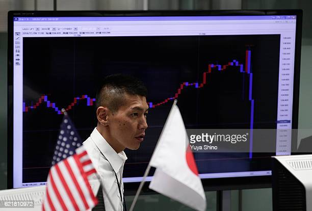 An employee of a foreign exchange trading company stands in front of a monitor displaying the graph of the recent fluctuations of the Japanese yen's...