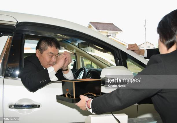 An employee of a funeral service company demonstrates on Dec 16 how mourners will be able to offer incense at a drivethru window set up at the...