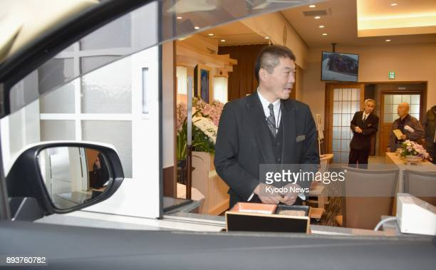 An employee of a funeral service company stands at a drivethru window set up at the Aishoden funeral home in Nagano Prefecture A first in Japan and...