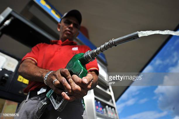 An employee of a gas station in Caracas Venezuela cleans a hose on February 17 2011 AFP PHOTO/MIGUEL GUTIERREZ