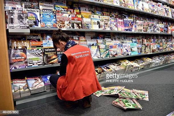 An employee of a newsstand puts magazines on display on February 25 2015 in Lille AFP PHOTO /PHILIPPE HUGUEN