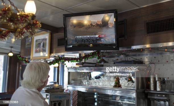An employee of a roadside restaurant watches a television news report December 14 2012 in Chatham New York of the killings of 26 elementary school...