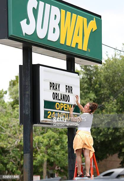 An employee of a Subway restaurant posts a message of support to the victims of a mass shooting in Orlando Florida on June 12 2016 Fifty people died...
