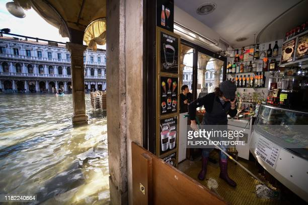 An employee of a takeaway food shop mops the floors while talking on the phone in an arcade of the flooded St Mark's Square on November 14 2019 in...