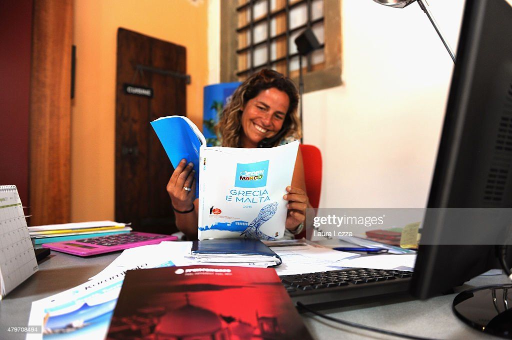 An employee of a travel agency sells a trip to Greece the day after Greece's austerity referendum which dominates the Italian front pages today, on July 6, 2015 in Livorno, Italy. Greeks voted in a strong majority against the reform plan proposed by the Troika, with Italian newspapers highlighting Prime Minsiter Alexis Tsipras's clear victory with the 'No' campaign.