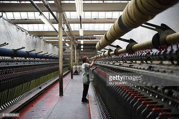 An employee of Abraham Moon and Sons woollen mill checks a spinning machine in Guiseley northern England on March 30 2016 Abraham Moon which was...