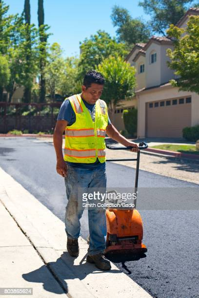 An employee of American Asphalt pulls a manual compactor across a newly laid road surface during a road construction and resurfacing project in the...