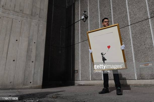 An employee of auction house Christie's poses with 'Girl with Balloon' by British street artist Banksy at the Southbank centre in London on August 30...