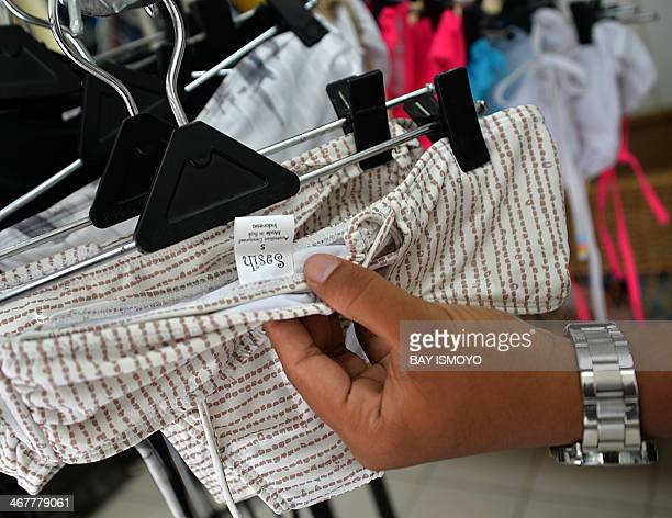 An employee of Australian drug trafficker Schapelle Corby's sister Mercedes Corby surfing and bikini shop shows the tag of the merchandise which was...
