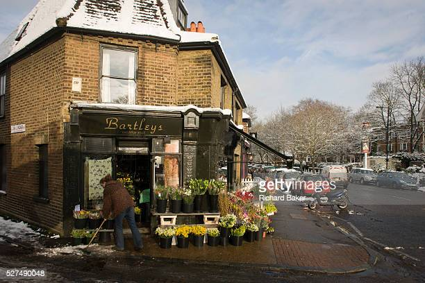 An employee of Bartleys the florist business in Dulwich Village south London brushes melting pavement snow Buckets of assorted blooms are on sale on...