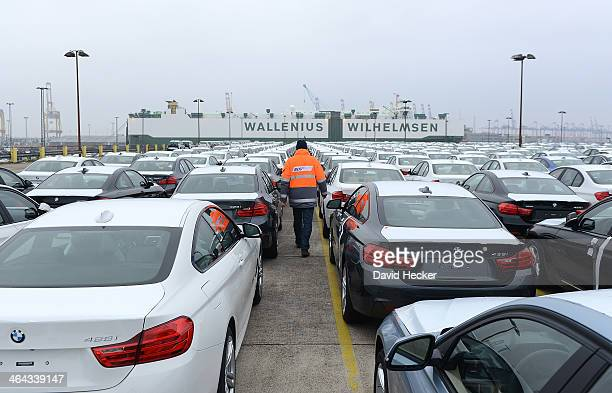 An employee of BLG Logistic Group walks along BMW cars destined for export overseas parked and waiting to be loaded onto ships on January 22 2014 in...