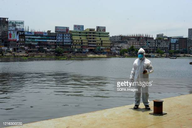 An employee of boat terminal is seen wearing a protective suit while monitoring as the boat terminal reopens after the Coronavirus lockdown crisis....