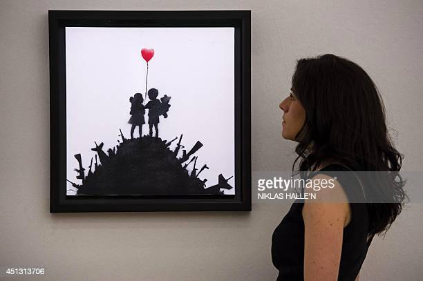An employee of Bonham's auction house examines Kids on Guns by Banksy during a press preview in London on June 27 ahead of the PostWar and...