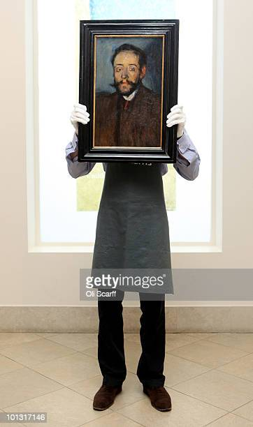 An employee of Bonhams auction house holds a painting by Pablo Picasso which features in their forthcoming Impressionist and Modern Art Sale on June...