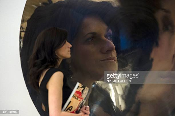 An employee of Bonham's auction house is reflected in an untitled stainless steel sculpture by Anish Kapoor during a press preview in London on June...