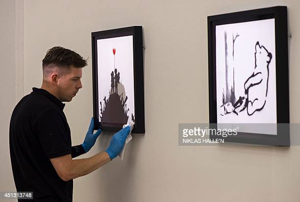 An employee of Bonham's auction house positions Kids on Guns by Banksy during a press preview in London on June 27 ahead of the PostWar and...