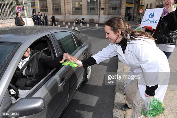 An employee of breathalyzer making firm Contralco distributes breathalyzer to a motorist on February 5 2013 in Gignac to protest against the 76...