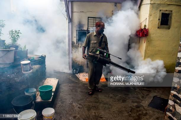 An employee of Brihanmumbai Municipal Corporation a city civic body sprays smoke during an antimalaria fumigation drive inside a slum in Mumbai on...