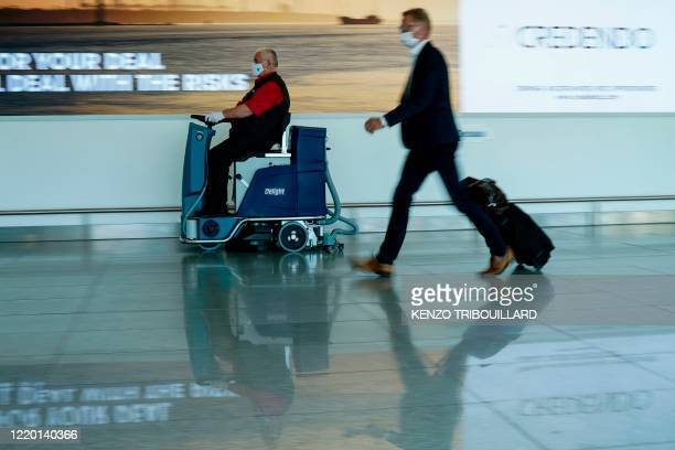 An employee of Brussels airport cleans up the floor at Brussels Airport, in Zaventem, on June 15, 2020 as Brussels Airport reopens for travels within...