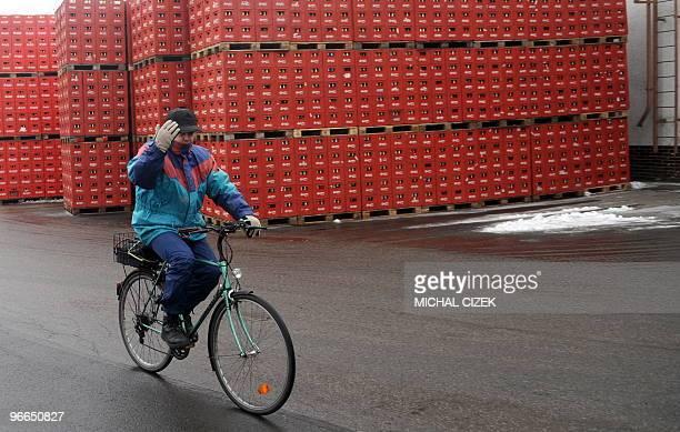 An employee of Budejovicky Budvar company greets as he rides his bicycle at the Budejovicky Budvar brewery on January 22 2010 in Ceske Budejovice...