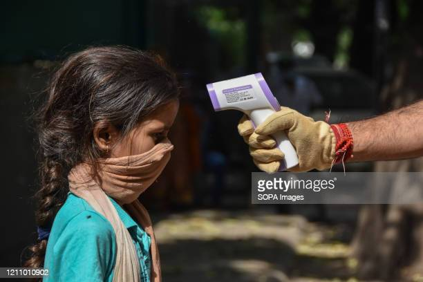 An employee of burger king holds up an infrared thermometer to screen a slum kid during the food distribution amid Coronavirus COVID 19 American...