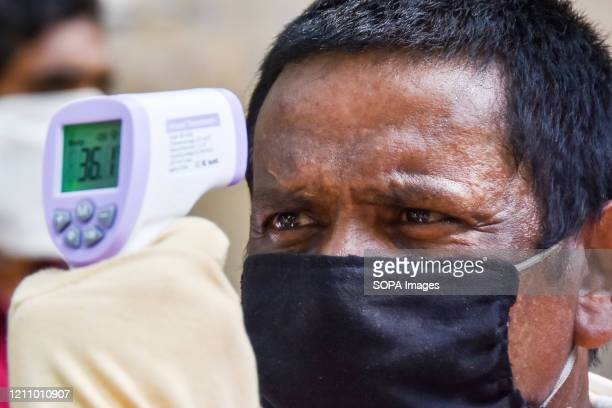 An employee of burger king holds up an infrared thermometer to screen a man during the food distribution amid Coronavirus COVID 19 American...