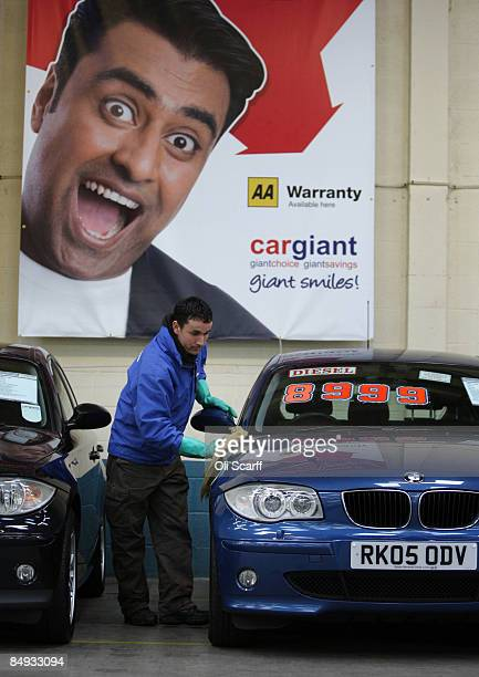 An employee of Cargiant the world's largest car supermarket cleans one of the thousands of cars on display in White City on February 18 2009 in...