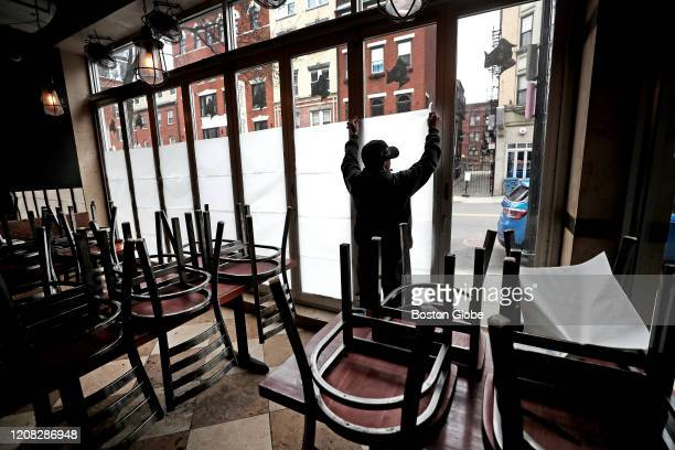 An employee of Carmelina's in the North End of Boston tapes up paper in the windows of the restaurant which is temporarily closing during the...